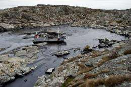 A small Swedish Coast Guard vessel sailing on a thick oil slick in Tjorn