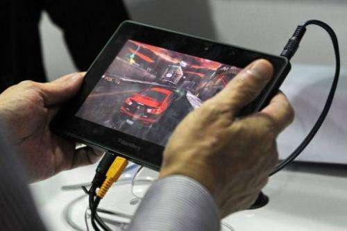 A visitor playing an online game with a Blackberry 'play book' at the CommunicAsia exhibition in Singapore