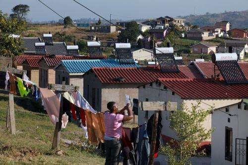 A woman hangs her laundry in the township of Demat where power company Eskom installed solar heaters on roofs