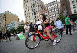 A young New York resident takes a test ride as part of a demonstration of a new bicycle sharing system