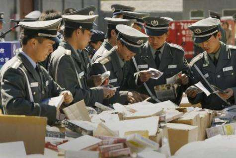 Beijing security personnel destroy counterfeit CD's and DVD's