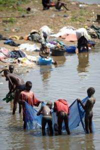 Boys use a net to fish while women wash clothes in the banks of the White Nile River