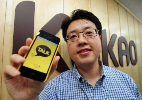 CEO of Kakao Talk Lee Jae-Beom poses in front of KAKAO Company's logo in Seoul