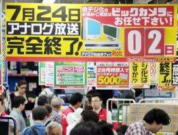 Consumers walk by a sign informing customers that two days remain before the country will end analog broadcasts