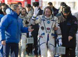 Dutch astronaut Andre Kuipers (centre) waves as he walks before boarding the Soyuz TMA-03M spacecraft