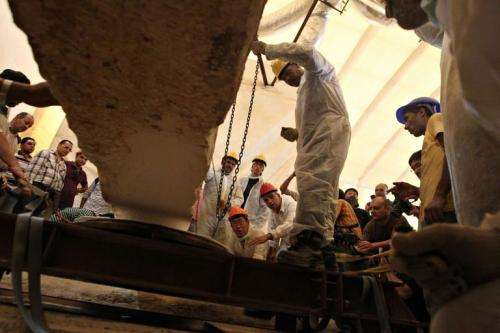 Egyptian workers remove a rock from the burial site of the second