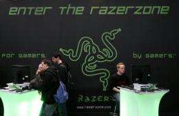 Fairgoers play video games in front of the stand of gaming peripherals producer