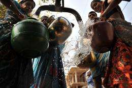 Indian women fill containers with potable water from a government water supply tanker