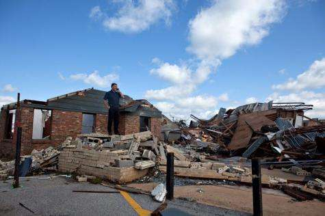 In the aftermath of a severe tornado, owner Frank Evans stands on the rubble that was the Quik Pawn Shop