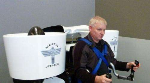 Jetpack inventor Glenn Martin sits with his creation strapped to his back in Christchurch