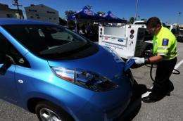 John Nielsen of the American Automobile Association (AAA) demonstrates charging a Nissan Leaf electric car