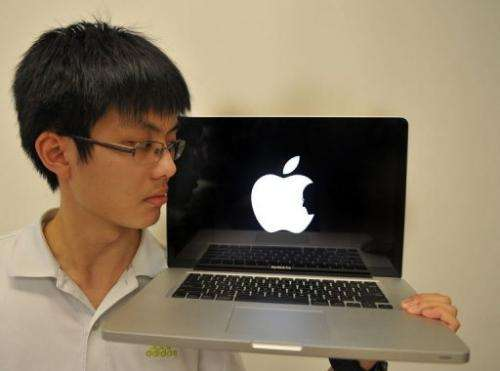 Jonathan Mak, a Hong Kong student poses with his laptop showing his logo in tribute of Apple founder Steve Jobs