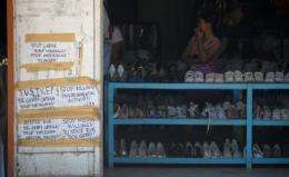 Messages seeking justice are posted at the clothing shop where environment activist Gerry Ortega was shot in Palawan