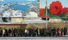 North Korean commuters wait for a bus beneath posters showing Mount Paekdu in Pyongyang