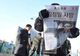 Pedestrians read a special edition a South Korean newspaper announcing the death of North Korean leader Kim Jong-Il