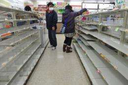 People look for food amid empty shelves in a shop in Fukushima