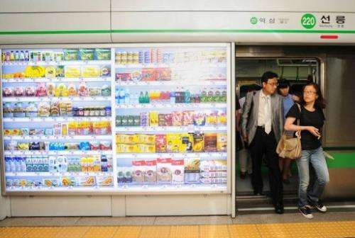 South Koreans get off a subway car next to a virtail retail shop (L) wall at Seolleung subway station in Seoul