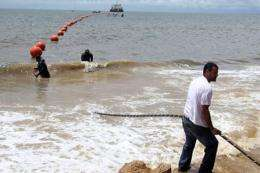 Technicians display the ACE fiber optic cable in October 2011, on the seashore of Libreville