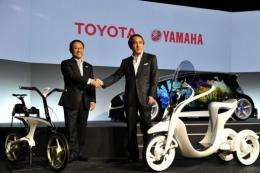 Toyota Motor and Yamaha Motor presidents display the electric commuter (R) and electric power assisted bicycle