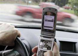 US urges ban on texting, talking while driving (AP)