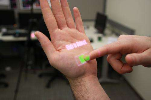 Wearable depth-sensing projection system makes any surface capable of multitouch interaction