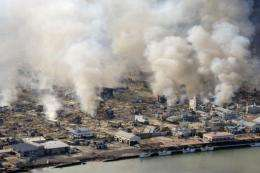 White smokes rises into the air in the badly damaged town of Yamada