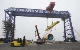 Workers prepare a wind turbine steel tower at the offshore terminal of the Offshore Base Cuxhaven