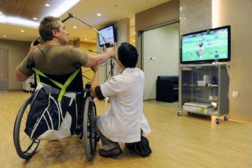 A patient recovering from stroke takes aim at a target with the help of senior occupational therapist Donald Xu Dong