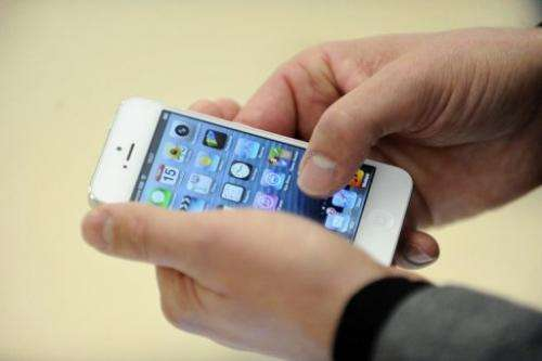 A person looks at an iPhone 5 on November 15, 2012 in Saint-Herblain, western France