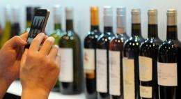 A visitor takes pictures of various bottles of red and white wine with his smartphone