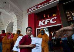 Greenpeace activists dressed as orangutans during a protest outside a KFC outlet in New Delhi on May 24