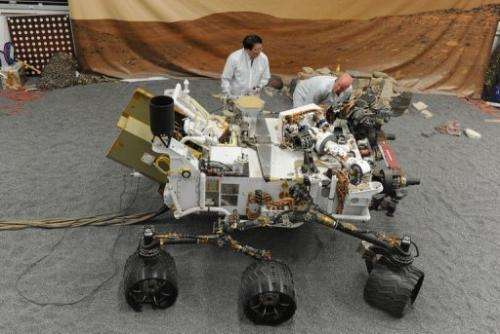 Jet Propulsion Laboratory (JPL) engineers examine a full size engineered model of the Mars rover Curiosity