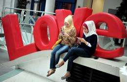 Two women enjoy social networking by using their mobile phone devices in Jakarta