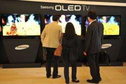 Visitors look at Samsung Electronics' new TVs that uses organic light-emitting diode (OLED) technology
