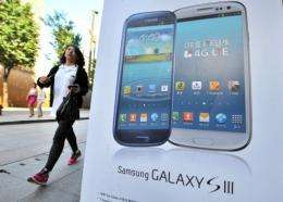 A woman walks past an advertisement for the Samsung Galaxy S3 at a mobile phone shop in Seoul on August 27, 2012