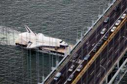 Space Shuttle Enterprise is carried by barge underneath the Verrazano-Narrows Bridge in New York City on June 3
