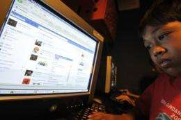Abdu Rauf, a 12 year old Indonesian Facebook user, logs on at an Internet shop in Jakarta