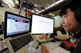 A Facebook User Operations team member checks a page of the website at the Facebook headquarters