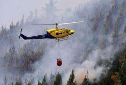 A helicopter carries a water bag to fight a massive forest fire affecting the commune of Ranquil