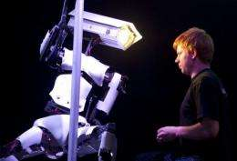 A man adjusts a pole dancing robot on the Tobit Software stand at the CeBIT IT fair