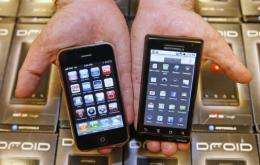 A manager holds an Apple iPhone (L) and Motorola's Droid smartphone (R)