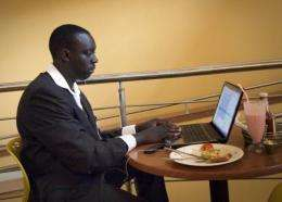 A man eats his lunch as he works on his laptop at an internet cafe in Kampala