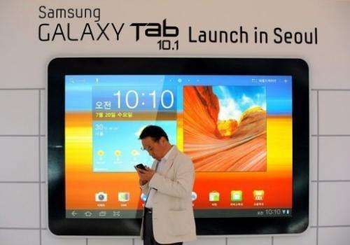A man stands in front of an advert for Samsung Electronics' new tablet computer in Seoul in 2011