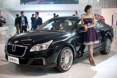 A model stands beside a 'B11' car by Chinese manufacturer Hawtai Motors, at the Auto China show in Beijing