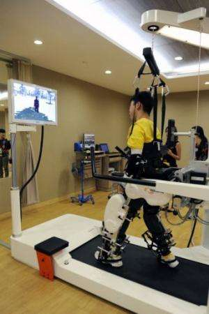 A patient who has cerebral palsy looks at his virtual avatar as he exercises on the Lokomat robotic gait trainer