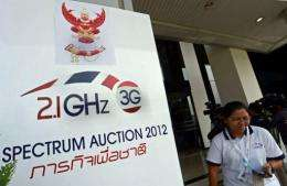 A Thai official walks past a sign of the 3G spectrum auction