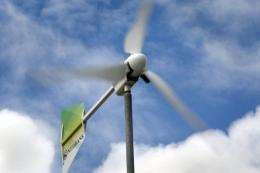 A wind turbine spins outside Africa's first bank branch partially powered by wind, in Du Noon