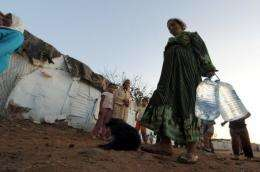 A woman carries bottles of tap water in a slum in the Moroccan town of Sale near Rabat
