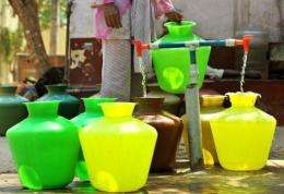 A woman collects drinking water in plastic pots from a community tap in Bangalore