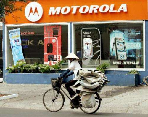 A woman rides past a Motorola shop in downtown Ho Chi Minh City